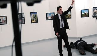 """A man identified as Mevlut Mert Altintas shouts after shooting Andrei Karlov, the Russian Ambassador to Turkey, at a photo gallery in Ankara, Turkey, Monday, Dec. 19, 2016. Shouting """"Don't forget Aleppo! Don't forget Syria!"""" Altintas fatally shot Karlov in front of stunned onlookers at a photo exhibit. (AP Photo/Burhan Ozbilici)"""