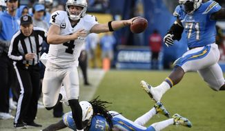 Oakland Raiders quarterback Derek Carr (4) reaches for a first down before going out of bounds as San Diego Chargers strong safety Jahleel Addae (37) and defensive tackle Kaleb Eulls (71) defend during the second half of an NFL football game Sunday, Dec. 18, 2016, in San Diego. (AP Photo/Denis Poroy)
