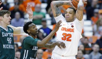 Syracuse's Dajuan Coleman, right, passes the ball under pressure from Eastern Michigan's Tim Bond, center, and Baylee Steele, left, in the first half of an NCAA college basketball game in Syracuse, N.Y., Monday, Dec. 19, 2016. (AP Photo/Nick Lisi)