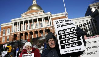 Protesters gather outside the Statehouse in Boston ahead of Massachusetts' Electoral College vote, Monday, Dec. 19, 2016. (AP Photo/Michael Dwyer)