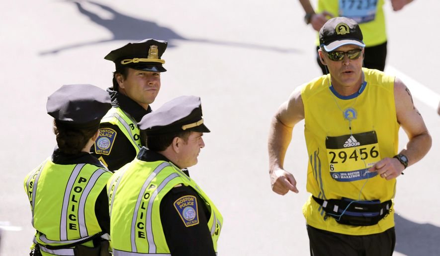 "FILE - In this April 18, 2016 file photo, actor Mark Wahlberg, center left, dressed as a Boston Police officer, watches runners cross the finish line as he films a scene for the ""Patriot's Day"" movie at the 120th Boston Marathon in Boston. Wahlberg's movie about the bombings during the 2013 Boston Marathon premiers in limited release on Wednesday, Dec. 21, in Boston, New York and Los Angeles, before a nationwide release on Jan. 13, 2017. (AP Photo/Charles Krupa, File)"