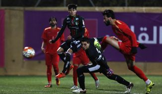 In this Thursday, Dec. 15, 2016 photo, Chile's Palestino players , in red, in action during friendly soccer match with Palestinian national squad in the West Bank city of Hebron. For the past week, Palestinians in the West Bank have been enjoying a special Christmas time present: the first ever visit by Chilean soccer club Deportivo Palestino. The team, founded a century ago by Palestinian immigrants in Chile, is boosting the local sports scene also bringing a great deal of symbolism. (AP Photo/Majdi Mohammed)