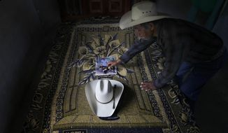 ADVANCE FOR USE FRIDAY, DEC. 23, 2016 AND THEREAFTER-In this July 15, 2016 photo, Wenceslao Rangel Gutierrez places a miniature horse statue on a photograph of his late son, Jose, next to his son's hat inside the newly built bedroom at their home in El Sabino, Mexico. The room and bed were paid for using money his son sent home from the U.S. while part of a guest worker program, and was meant as a surprise for him. Jose never got to see his new room, killed in a bus accident when he was on his way back home. (AP Photo/Marco Ugarte)
