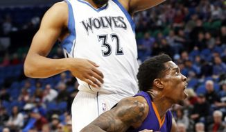 Phoenix Suns' Eric Bledsoe, right, eyes the basket as he drives by Minnesota Timberwolves' Karl-Anthony Towns during the first quarter of an NBA basketball game, Monday, Dec. 19, 2016, in Minneapolis. (AP Photo/Jim Mone)