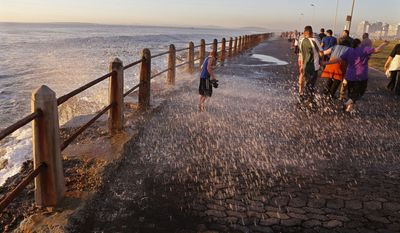 FILE - This Aug. 24, 2014 file photo shows a child sprayed by a wave on the promenade, a popular tourist hotspot near the city of Cape Town, South Africa. Cape Town is turning up on some lists for places to go in 2017, partly because exchange rates make it affordable and also because a new contemporary arts museum is opening in the fall. (AP Photo/Schalk van Zuydam, File)