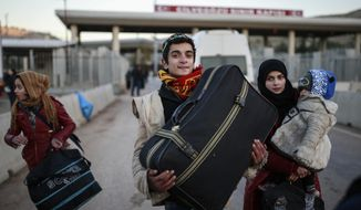 Members of a Syrian family carry their belongings after they crossed into Turkey at the Cilvegozu border gate with Syria, near Hatay, southeastern Turkey, Sunday, Dec, 18, 2016. Several people were able to cross into Turkey after they managed to leave the embattled Syrian city during the ceasefire, and arrived to Turkey by their own means. The Aleppo evacuation was suspended Friday after a report of shooting at a crossing point into the enclave by both sides of the conflict. (AP Photo/Emrah Gurel)