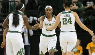 Baylor's Dekeiya Cohen, left, and Natalie Chou (24) celebrate a basket scored by Khadijiah Cave, center, in the first half of an NCAA college basketball game against Winthrop on Thursday, Dec. 15, 2016, in Waco, Texas. Cave led all scoring with 25 points in the 140-32 Baylor win. (AP Photo/Tony Gutierrez)