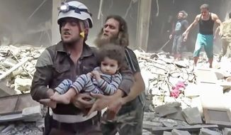A civil defense worker carries a child after airstrikes hit Aleppo, Syria. (Associated Press)