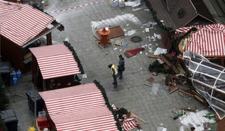 Police officers inspect the crime scene in Berlin, Germany, Tuesday, Dec. 20, 2016, the day after a truck ran into a crowded Christmas market and killed several people. (AP Photo/Markus Schreiber)