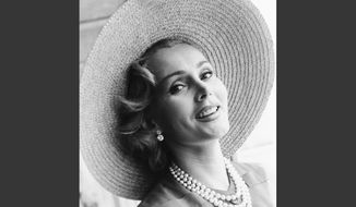 FILE - In a July 14, 1955 file photo, Zsa Zsa Gabor arrives at London Airport from Paris, in a Crimson dress and a straw hat. Gabor died Sunday, Dec. 18, 2016, of a heart attack at her Bel-Air home, her husband, Prince Frederic von Anhalt, said. She was 99. (AP Photo)