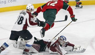 Colorado Avalanche goalie Semyon Varlamov of Russia makes a diving save of a shot as Minnesota Wild's Eric Staal, top, jumps over him during the first period of an NHL hockey game Tuesday, Dec. 20, 2016, in St. Paul, Minn. (AP Photo/Jim Mone)