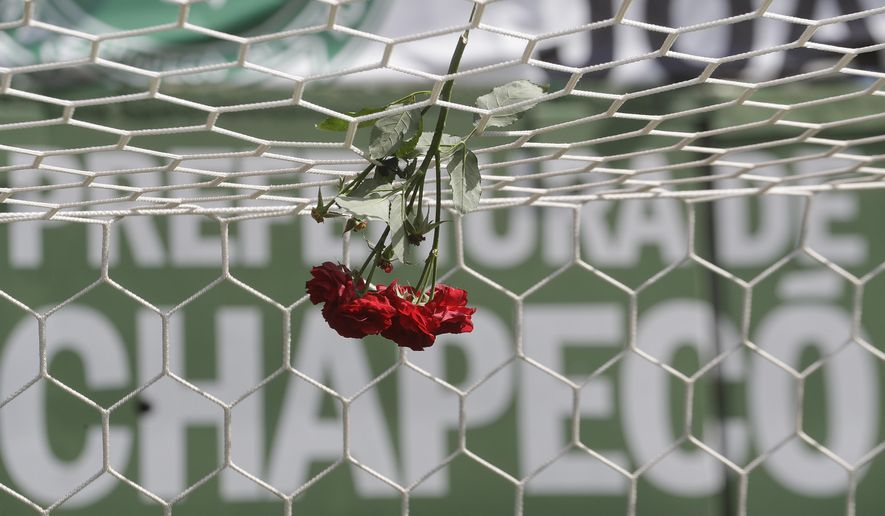 FILE - In this Nov. 29, 2016 file photo, flowers hang from a soccer net at the Arena Conda stadium in Chapeco, Brazil. Colombia and Brazil have scheduled a friendly match on Jan. 25, 2017 to raise money for the victims of the air crash last month that killed 19 players on Brazil's Chapecoense football club. (AP Photo/Andre Penner, File)