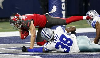 Tampa Bay Buccaneers wide receiver Adam Humphries (11) holds on to the ball as he goes to the ground over Dallas Cowboys' Brandon Carr (39) after catching a pass for at touchdown in the second half of an NFL football game, Sunday, Dec. 18, 2016, in Arlington, Texas. (AP Photo/Michael Ainsworth)