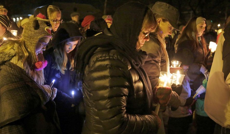 FILE - In this Jan. 29, 2016 file photo, people hold candles in memory of the three deceased Sheboygan Falls children at River Park in Sheboygan Falls, Wis. Natalie Renee Martin, 11, Carter Maki, 7, and Benjamin Martin, 10, died in a house fire Jan. 26. Natalie, who died saving the lives of even younger children, is among 21 people being honored with Carnegie medals for heroism. The Carnegie Hero Fund Commission, based in Pittsburgh, announced the winners Tuesday, Dec. 20. (Gary C. Klein/The Sheboygan Press via AP)