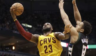 Cleveland Cavaliers' LeBron James shoots over Milwaukee Bucks' Malcolm Brogdon during the first half of an NBA basketball game Tuesday, Dec. 20, 2016, in Milwaukee. (AP Photo/Morry Gash)