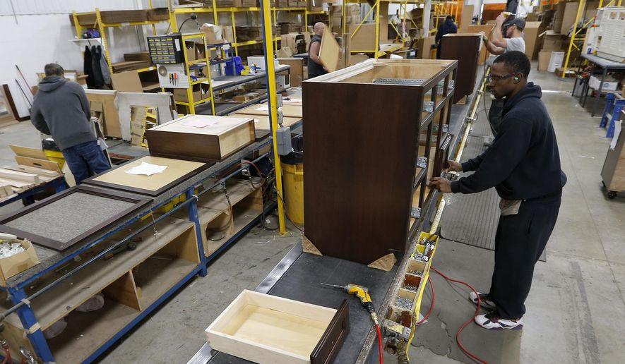 Beau Joe Battles Installs Drawers In A Cabinet At Bertch Cabinet In Waterloo,  Iowa, Thursday