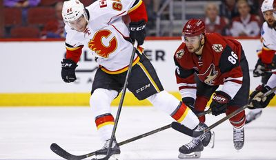 Calgary Flames right wing Garnet Hathaway (64) beats Arizona Coyotes right wing Josh Jooris (86) to the puck during the first period of an NHL hockey game Monday, Dec. 19, 2016, in Glendale, Ariz. (AP Photo/Ross D. Franklin)