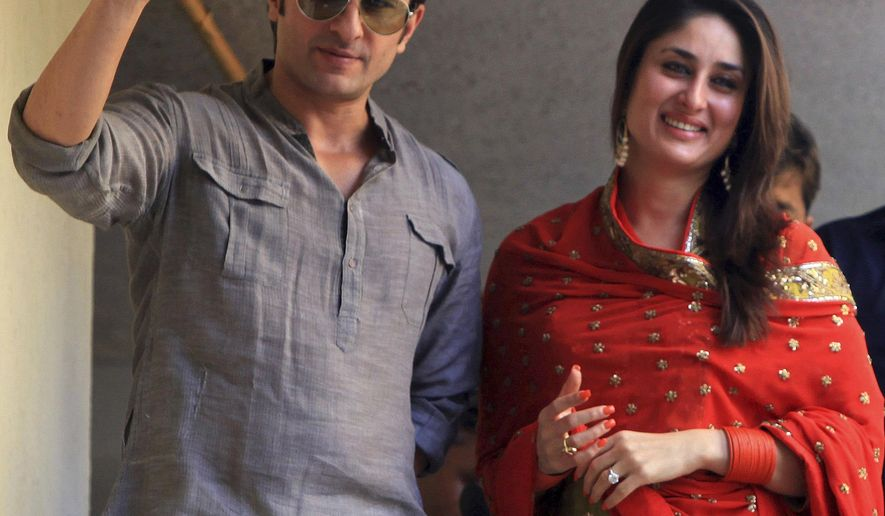FILE - In this Oct. 16, 2012 file photo, Bollywood stars Saif Ali Khan, left, and Kareena Kapoor step out on a balcony to greet waiting fans after getting married in Mumbai, India. The popular Bollywood couple say they have been blessed with a baby boy. The couple announced the birth of their son in a Mumbai hospital in a tweet on Tuesday, Dec. 20, 2016. (AP Photo/Rajanish Kakade)