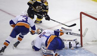 New York Islanders goalie Thomas Greiss (1) knocks the puck clear as Boston Bruins left wing Brad Marchand (63) looks for the rebound during the third period of an NHL hockey game in Boston, Tuesday, Dec. 20, 2016. The Islanders defeated the Bruins 4-2. At left is New York Islanders defenseman Travis Hamonic (3). (AP Photo/Charles Krupa)