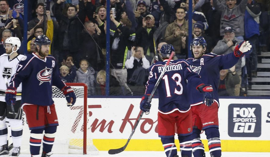 Columbus Blue Jackets' Brandon Dubinsky, left to right, Cam Atkinson, and Boone Jenner celebrate their goal against the Los Angeles Kings during the third period of an NHL hockey game Tuesday, Dec. 20, 2016, in Columbus, Ohio. The Blue Jackets beat the Kings 3-2 in a shootout. (AP Photo/Jay LaPrete)