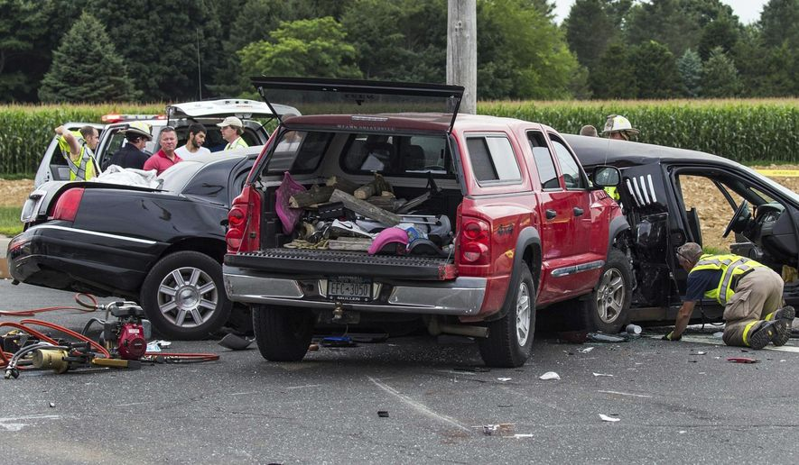 FILE - In this July 18, 2015, file photo, authorities investigate the scene of a fatal crash between a limousine and sports utility vehicle in Cutchogue, N.Y. A special grand jury empaneled after the fatal crash that killed four women in the limousine as it was leaving a New York winery has issued a report calling for better safety regulations for stretch limousines. The report said cars converted into limos often lack safety components, like side-impact airbags, reinforced rollover protection bars and accessible emergency exits, that are required in smaller vehicles. (Randee Daddona/Newsday via AP, File)