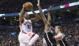 Toronto Raptors guard DeMar DeRozan, left, shoots on Brooklyn Nets forward Rondae Hollis-Jefferson, center, during second half NBA basketball action in Toronto on Tuesday, Dec. 20, 2016. (Chris Young/The Canadian Press via AP)