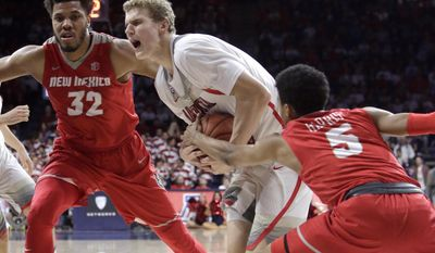 Arizona forward Lauri Markkanen drives between New Mexico forward Tim Williams (32) and Jalen Harris (5) during the second half of an NCAA college basketball game, Tuesday, Dec. 20, 2016, in Tucson, Ariz. (AP Photo/Rick Scuteri)