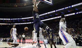 New Orleans Pelicans' Anthony Davis (23) dunk the ball over Philadelphia 76ers' Joel Embiid (21) during the first half of an NBA basketball game, Tuesday, Dec. 20, 2016, in Philadelphia. (AP Photo/Matt Slocum)