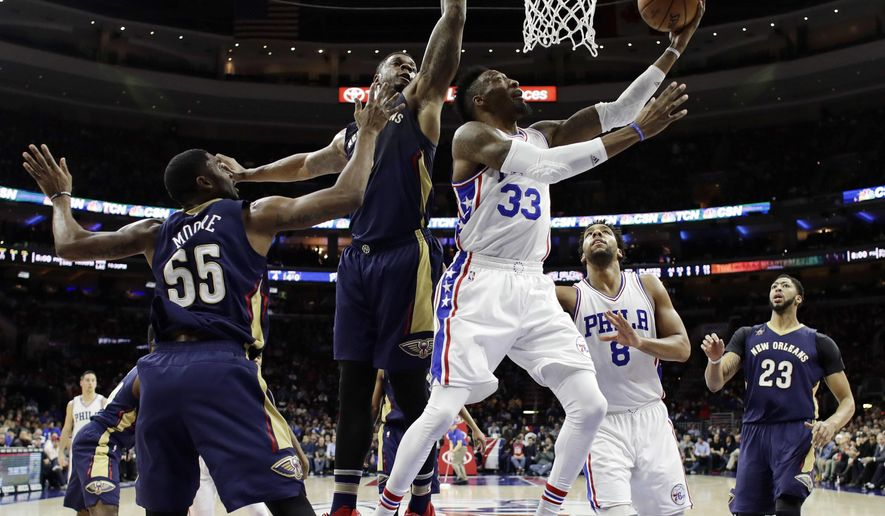 Philadelphia 76ers' Robert Covington, center, goes up for a shot past New Orleans Pelicans' E'Twaun Moore, from left, and Terrence Jones during the first half of an NBA basketball game, Tuesday, Dec. 20, 2016, in Philadelphia. (AP Photo/Matt Slocum)