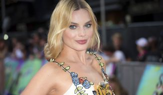 "FILE - In this Aug. 3, 2016 file photo, actress Margot Robbie poses for photographers upon arrival at the European Premiere of ""Suicide Squad,"" in London. Robbie has responded to wedding rumors by giving the finger on Instagram. Robbie posted a picture of a big diamond on her extended ring finger on the photo sharing platform Monday, Dec. 19, 2016. (AP Photo/Joel Ryan, File)"