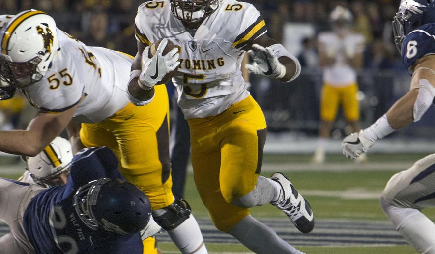 FILE - In this Oct. 22, 2016, file photo, Wyoming running back Brian Hill runs in the first half of an NCAA college football game against Nevada, in Reno, Nev. Wyoming meets BYU in the Poinsetta Bowl on Wednesday.  (AP Photo/Tom R. Smedes, File)