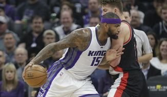 Sacramento Kings forward DeMarcus Cousins, left, goes to the basket against Portland Trail Blazers' Meyers Leonard during the first quarter of an NBA basketball game Tuesday, Dec. 20, 2016, in Sacramento, Calif. (AP Photo/Rich Pedroncelli)