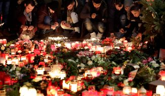 Sorrow: Mourners held a vigil Wednesday, two days after a lone-wolf terrorist used a truck to carry out a massacre at a Christmas market in Berlin. (Associated Press)