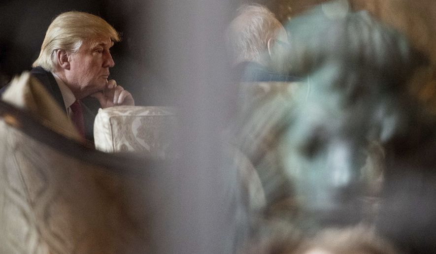 A metal lion is seen in reflection, right as President-elect Donald Trump, left, attends a meeting at Mar-a-Lago, in Palm Beach, Fla., Wednesday, Dec. 21, 2016. (AP Photo/Andrew Harnik)