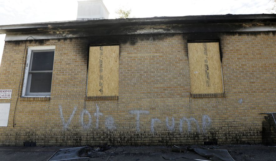 Boarded windows align Hopewell Missionary Baptist Church in Greenville, Miss., on Nov. 22 after it was burned and vandalized. (Associated Press)