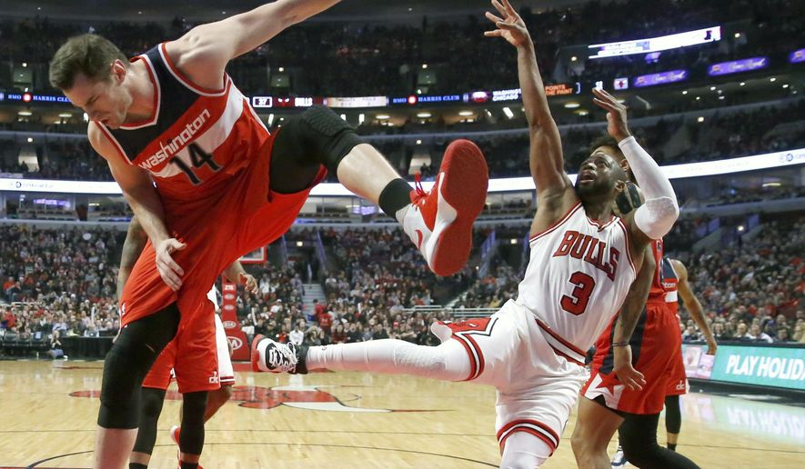 Chicago Bulls' Dwyane Wade (3) shoots as Washington Wizards' Jason Smith tries to defend during the first half of an NBA basketball game Wednesday, Dec. 21, 2016, in Chicago. (AP Photo/Charles Rex Arbogast)