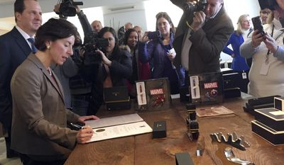 Rhode Island Gov. Gina Raimondo, left, signs a formal business citation at A.T. Cross Co.'s new flagship retail store, Wednesday, Dec. 21, 2016, in Providence, R.I. The 170-year-old maker of high-end pens recently moved its headquarters to Providence from suburban Lincoln, R.I. (AP Photo/Matt O'Brien)