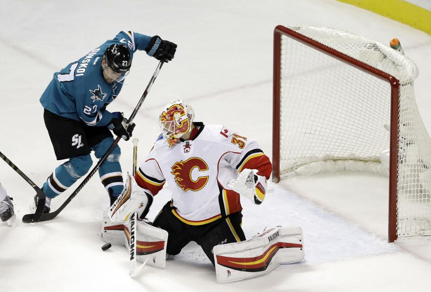 Calgary Flames' Chad Johnson, right, deflects a shot next to San Jose Sharks' Joonas Donskoi during the first period of an NHL hockey game Tuesday, Dec. 20, 2016, in San Jose, Calif. (AP Photo/Marcio Jose Sanchez)
