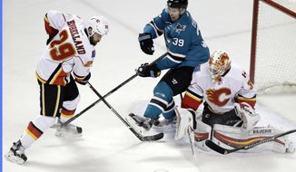 San Jose Sharks' Logan Couture (39) eyes the puck between Calgary Flames' Deryk Engelland (29) and goalie Chad Johnson during the first period of an NHL hockey game Tuesday, Dec. 20, 2016, in San Jose, Calif. (AP Photo/Marcio Jose Sanchez)