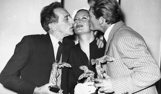 FILE - In this April 8, 1951 file photo, Jean Cocteau, left, and Jean Marais kiss Michele Morgan whilst holding their awards at Cannes Film Festival in France. Michele Morgan, a French actress who starred with Humphrey Bogart and Frank Sinatra and whose sea blue eyes captivated French audiences for decades, has died at 96. (AP Photo/File)