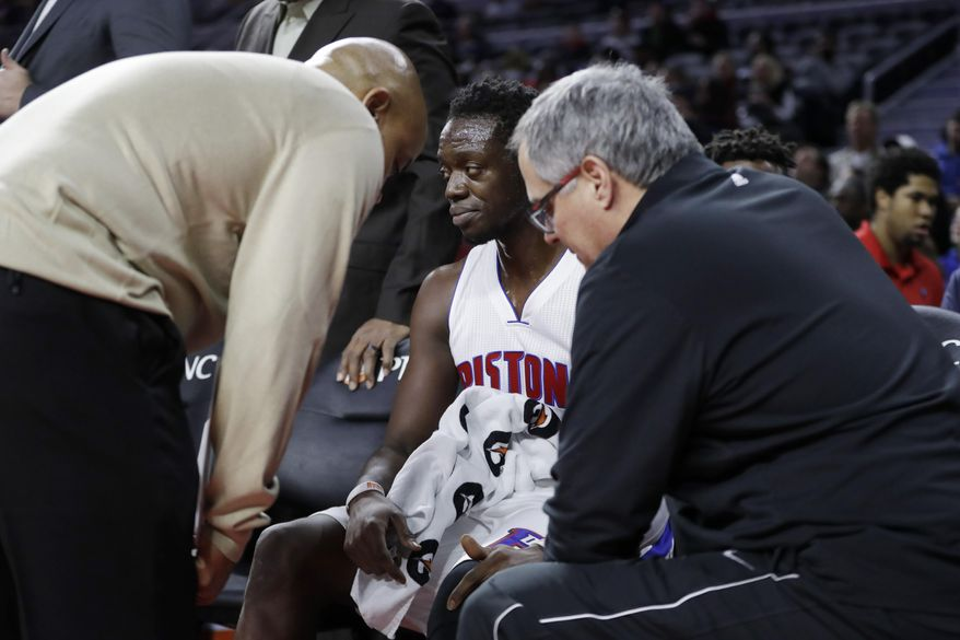 Detroit Pistons guard Reggie Jackson is checked by team officials before briefly returning to the locker room during the first half of an NBA basketball game against the Memphis Grizzlies, Wednesday, Dec. 21, 2016 in Auburn Hills, Mich. (AP Photo/Carlos Osorio)