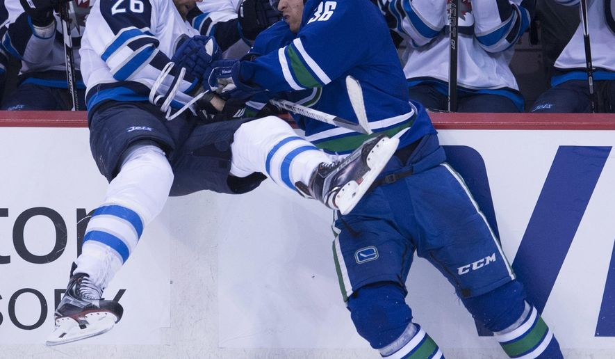 Vancouver Canucks right wing Jannik Hansen (36) puts Winnipeg Jets right wing Blake Wheeler (26) into the boards during the second period of an NHL hockey game Tuesday, Dec. 20, 2016, in Vancouver, British Columbia. (Jonathan Hayward/The Canadian Press via AP)