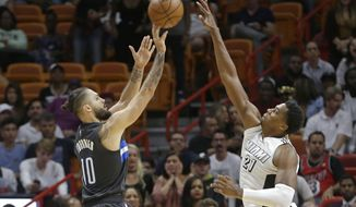 Orlando Magic guard Evan Fournier (10) shoots as Miami Heat center Hassan Whiteside (21) defends during the second overtime of an NBA basketball game, Tuesday, Dec. 20, 2016, in Miami. The Magic won 136-130. (AP Photo/Alan Diaz)