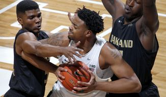 Michigan State's Nick Ward, center, is pressured by Oakland's Stevie Clark, left, and Xavier Hill-Mais, right, during the first half of an NCAA college basketball game, Wednesday, Dec. 21, 2016, in East Lansing, Mich. (AP Photo/Al Goldis)