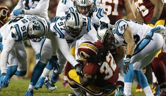 In this Monday, Dec. 19, 2016 photo, Washington Redskins running back Rob Kelley (32) is overwhelmed by the Carolina Panthers defense during the second half of an NFL football game in Landover, Md.   With their playoff hopes at stake, the Redskins want to get back to a balanced offense Saturday at the Bears.   (AP Photo/Alex Brandon)