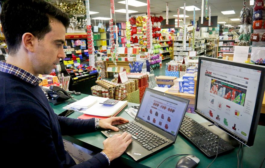 In this Thursday, Dec. 15, 2016, photo, Andrew Jacobs, owner of JAM Paper and Envelope, goes online to the company's e-commerce site, in New York. JAM now gets so much of its revenue online that the company has scaled back from five stores to a single Manhattan location, Jacobs says. (AP Photo/Bebeto Matthews)