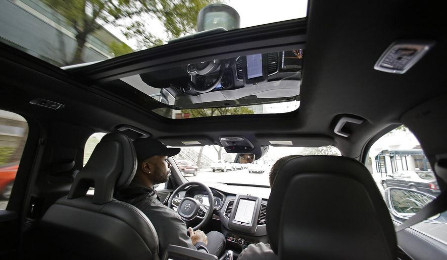 FILE - In this Tuesday, Dec. 13, 2016, file photo, Devin Greene sits in the front seat of an Uber driverless car during a test drive in San Francisco. Uber has pulled its self-driving cars from California roads. The ride-sharing company said Wednesday, Dec. 21, 2016, California transportation regulators revoke registrations for the vehicles. The DMV confirmed that it had moved to revoke the registrations of 16 cars, saying officials had been determined that the registrations were improperly issued because the vehicles were not properly marked as test vehicles. (AP Photo/Eric Risberg, File)