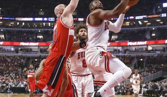 Chicago Bulls' Dwyane Wade, right, drives past Washington Wizards' Marcin Gortat during the first half of an NBA basketball game Wednesday, Dec. 21, 2016, in Chicago. (AP Photo/Charles Rex Arbogast)