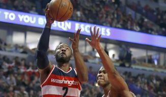 Washington Wizards' John Wall (2) drives and scores past Chicago Bulls' Cristiano Felicio during the first half of an NBA basketball game Wednesday, Dec. 21, 2016, in Chicago. (AP Photo/Charles Rex Arbogast)