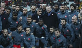 Turkey's President Recep Tayyip Erdogan, centre poses for pictures with managers and players prior to what the organisers said was a soccer match between Turkey's soccer stars against terrorism, in Istanbul, Thursday, Dec. 22, 2016. The match, arranged by the Turkish Football Federation consisted of two all-star teams facing each other made of players from teams competing in Turkish Super League. All ticket revenue will be handed over to the families of people who died in recent bomb attacks in Istanbul and Kayseri. (AP Photo)